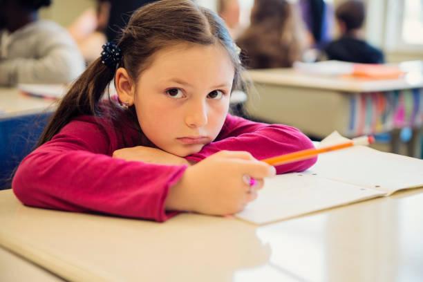 Porträt von traurigen kleinen Mädchen in Klassenzimmer, sitzt an ihrem Schreibtisch. – Foto