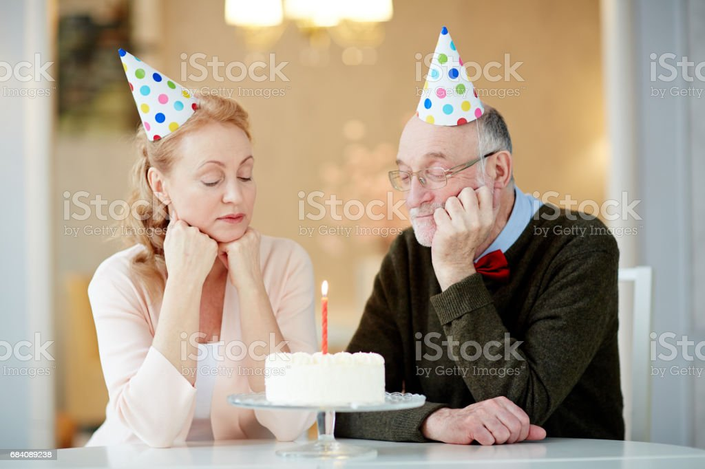 Portrait Of Sad Lonely Senior Couple Sitting Together At Table With