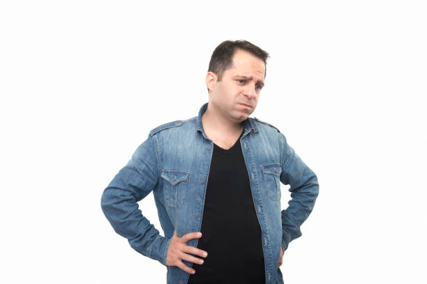 Portrait of sad man looking away with bored facial expression over white background stock photo