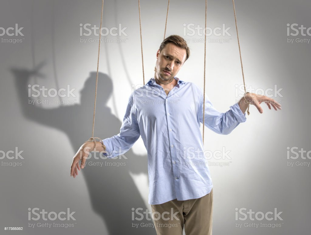 portrait of sad man on manipulating ropes with shadow of puppeteer behind isolated on grey stock photo