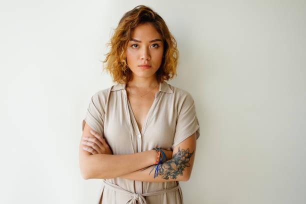 porträt von traurigen oder ernsten jungen frau im studio - tattoos frauen arm stock-fotos und bilder