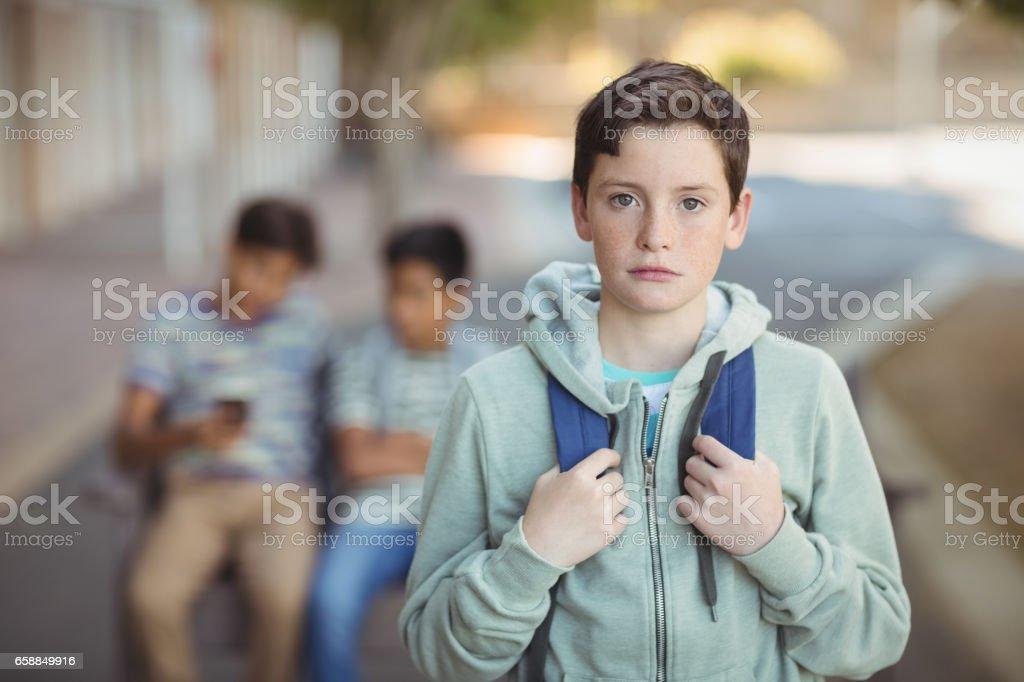 Portrait of sad schoolboy with schoolbag standing in campus stock photo
