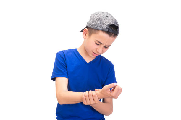 Portrait of sad teenage boy having wrist pain on white background