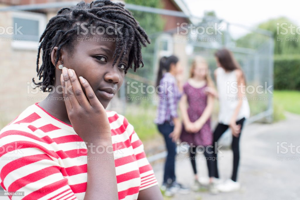 Portrait Of Sad Teenage Girl Feeling Left Out By Friends stock photo