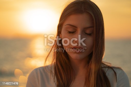 Beautiful woman is standing by the sea with eyes closed at sunset.