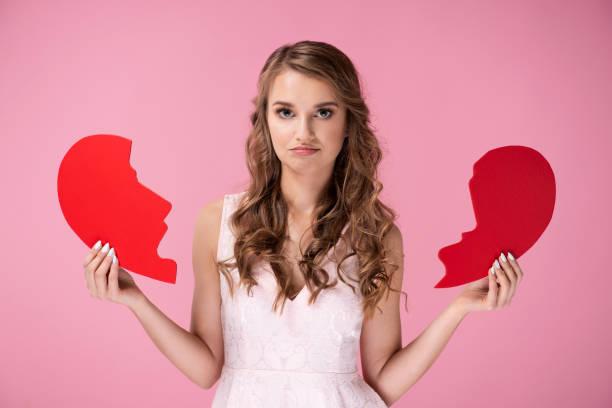 Portrait of sad woman holding broken heart stock photo