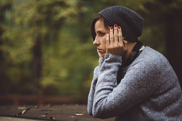 portrait of sad woman sitting alone in the forest. solitude - low contrast stock pictures, royalty-free photos & images