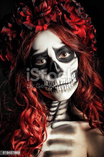 Closeup portrait of a sad young girl with muertos makeup (sugar skull)