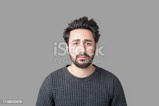 istock Portrait of sad young man looking at camera with frustrated facial expression against gray background 1148040425