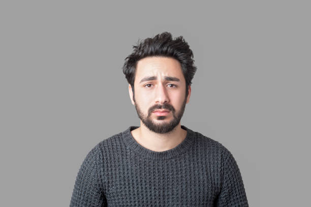 Portrait of sad young man looking at camera with frustrated facial expression against gray background stock photo