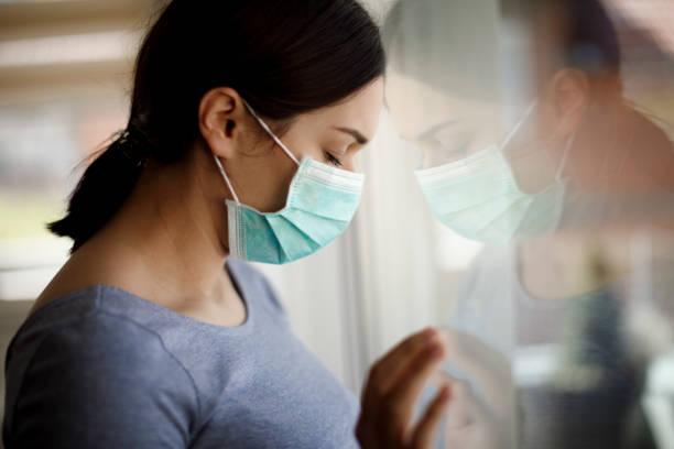 Porträt einer traurigen jungen Frau mit Gesichtsschutzmaske im Krankenhaus – Foto