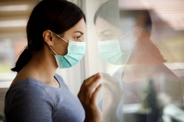 Portrait of sad young woman with face protective mask looking through the window at home stock photo