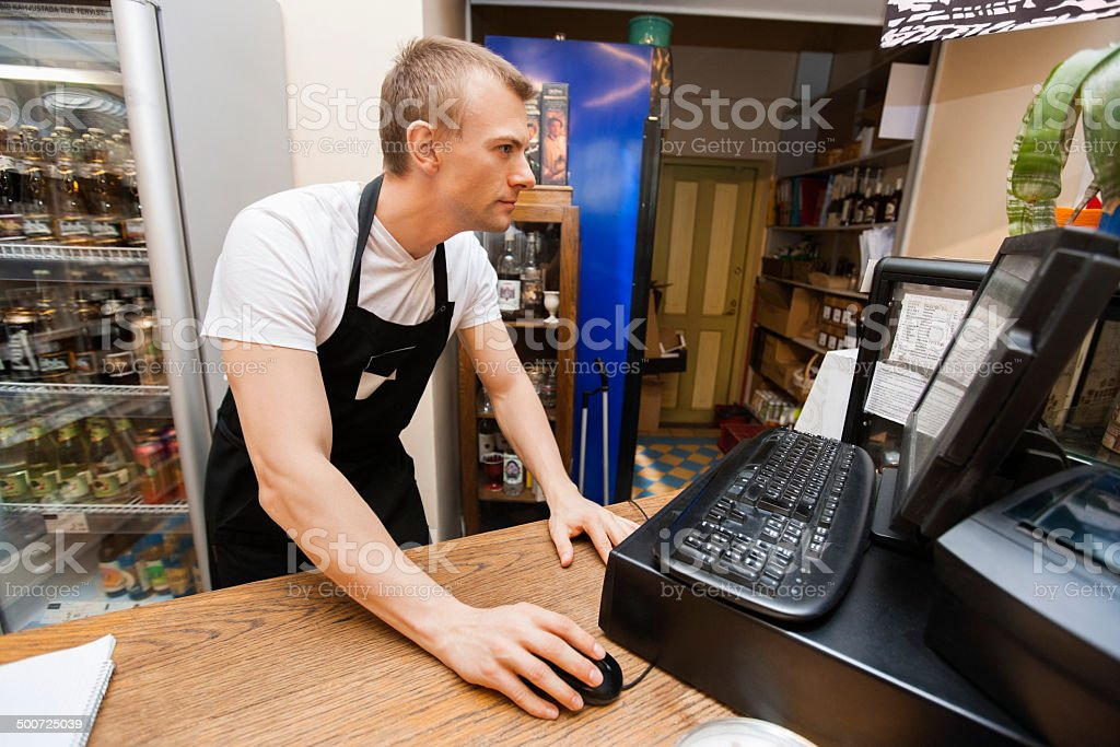 Portrait of salesman using computer at cash counter in supermarket stock photo