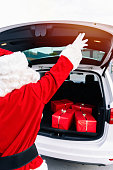 Portrait of Santa Claus closing the trunk of the open car full of gifts for delivery in the Christmas of 2020