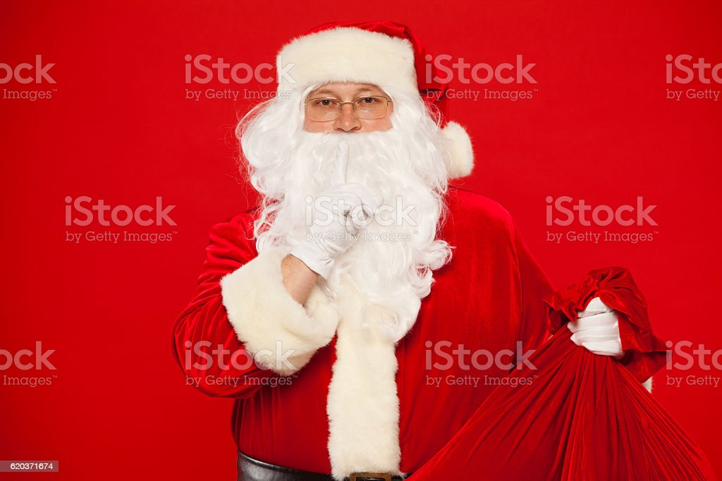 Portrait of Santa Claus with huge red sack keeping forefinger zbiór zdjęć royalty-free