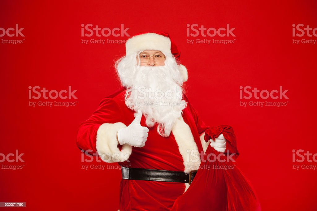 Portrait of Santa Claus with huge red sack thumb looking zbiór zdjęć royalty-free