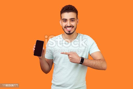 istock Portrait of satisfied brunette man pointing at cellphone and smiling at camera. indoor studio shot isolated on orange background 1190506771