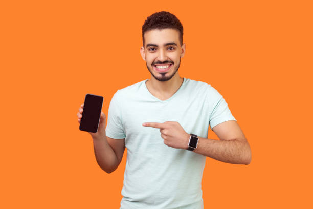 Portrait of satisfied brunette man pointing at cellphone and smiling at camera. indoor studio shot isolated on orange background stock photo