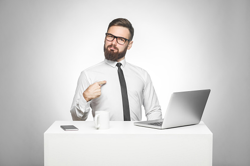 istock Portrait of satisfied confident smiling bearded young manager in white shirt and black tie are sitting in office are prouded of himself for achieved goals in work. 1147103315