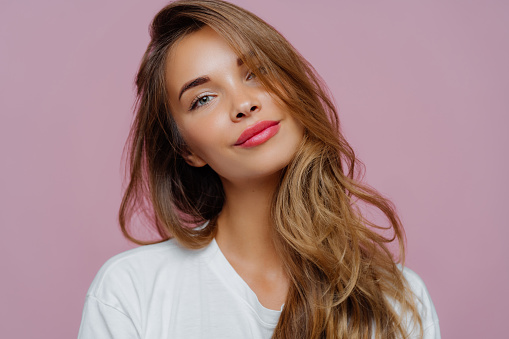 Portrait of satisfied relaxed young female model tilts head, has makeup, fair hair, dressed in white clothes, poses against purple background, has well cared complexion. People, beauty, face care