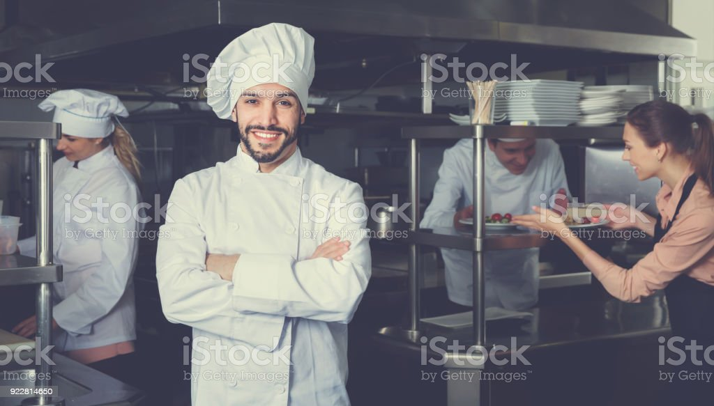 Portrait of satisfied smiling chef on restaurant kitchen stock photo