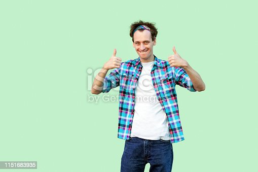 Portrait of satisfied young man in casual blue checkered shirt and headband standing, thumbs up and looking at camera with toothy smile. indoor studio shot, isolated on light green background.