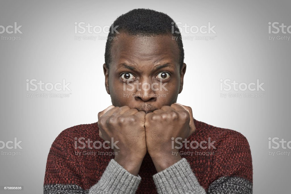 Portrait of scared young African American man dressed in sweater keeping hands in fists, holding them in front of his face, looking at camera with shocked and frightened expression. Fear concept. stock photo