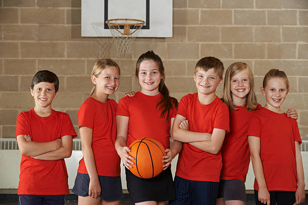 Portrait Of School Basketball Team In Gym stock photo