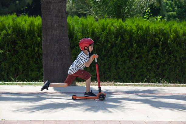 Portrait Of School Boy Riding Kick Scooter stock photo