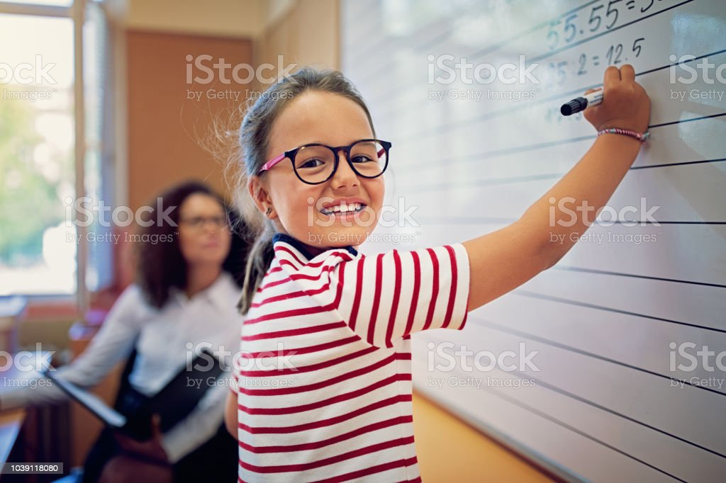 Portrait of school girl writing on the board in the classroom zbiór zdjęć royalty-free