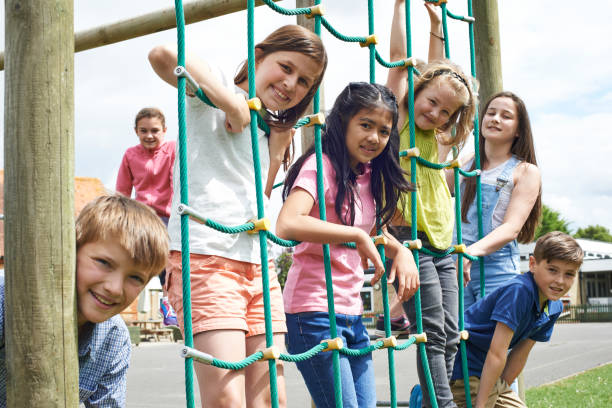 portrait of school pupils playing on climbing frame - recess stock photos and pictures