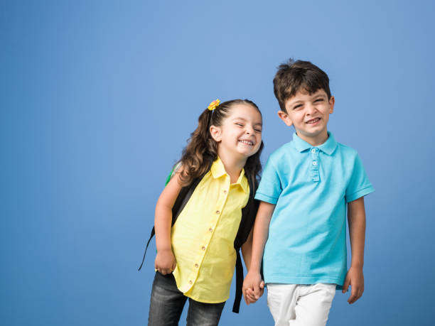 portret van scholier en schoolmeisje hand in hand voor blauwe achtergrond - zwarte spijkerbroek stockfoto's en -beelden