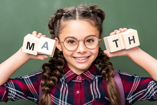 1016623732 istock photo portrait of schoolchild holding wooden cubes with word math near blackboard 1016623676