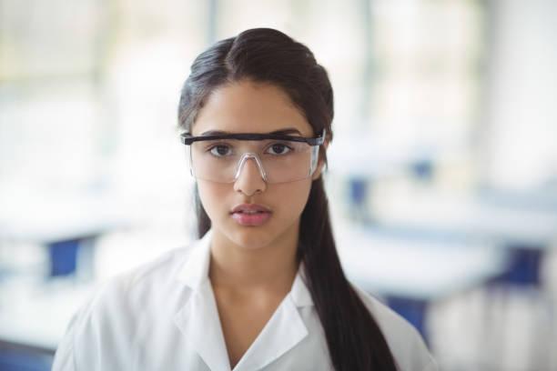 Retrato de menina vestindo óculos de proteção em laboratório de - foto de acervo