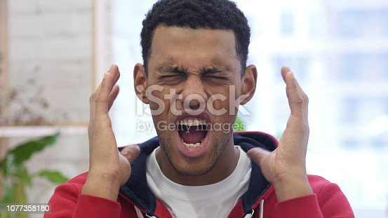 626964348istockphoto Portrait of Screaming Afro-American Man going Crazy 1077358180
