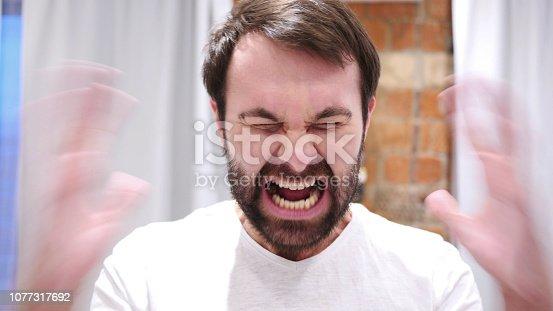 626964348istockphoto Portrait of Screaming Beard Man going Crazy, Indoor 1077317692