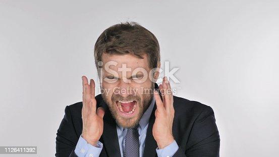 626964348istockphoto Portrait of Screaming Businessman going Crazy 1126411392