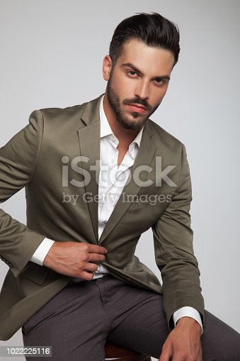 portrait of seated handsome man wearing a green suit on light grey background