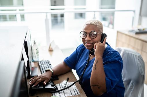Portrait of secretary talking on telephone at hospital reception