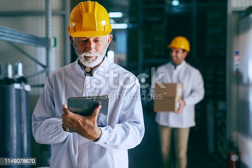 istock Portrait of senior adult warehouse worker in white uniform and with helmet on head using tablet. In background younger worker carrying boxed with goods. 1149078670
