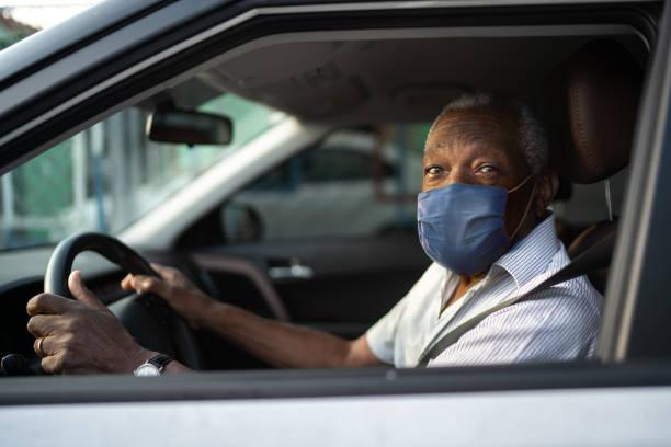 porträt eines älteren afrikanischen mannes, der ein auto mit gesichtsmaske fährt - berufsfahrer stock-fotos und bilder