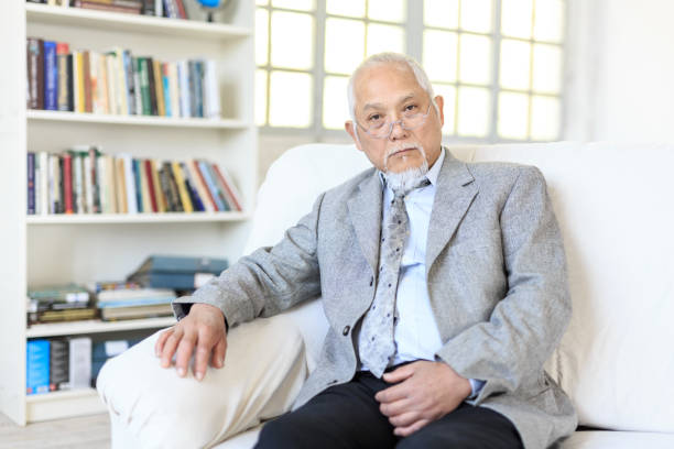 Portrait of senior asian man Portrait of mature asian man sitting on sofa at home. old asian male boss in the office stock pictures, royalty-free photos & images