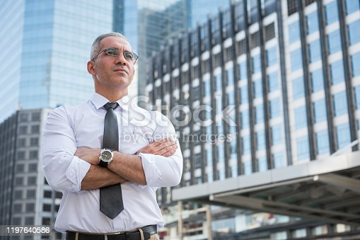 891418990 istock photo Portrait of senior businessman doing thinking,smiling,arm cross on building business background 1197640586