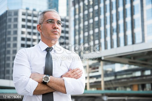 891418990 istock photo Portrait of senior businessman doing thinking,smiling,arm cross on building business background 1216776064