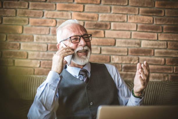portrait of senior businessman talking phone. - pensionati lavoratori foto e immagini stock