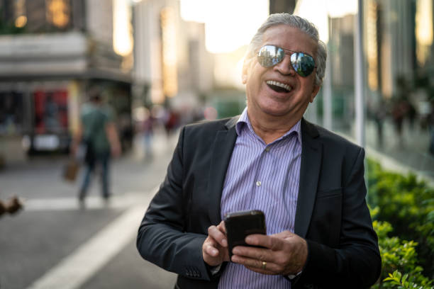 Portrait of senior businessman using mobile at city Looking at camera only senior men stock pictures, royalty-free photos & images
