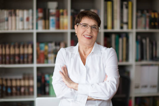 portrait of  senior businesswoman wearing glasses head shot in a white shirt, crossed hands looking at the camera with a warm friendly smile against the background of a bookcase - professore foto e immagini stock