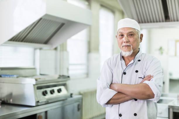 Portrait of senior chef in kitchen stock photo