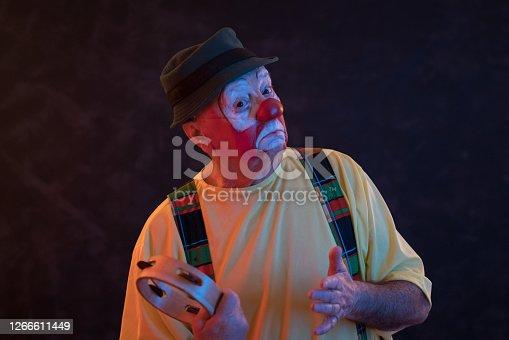 istock Portrait of senior clown in neon light 1266611449