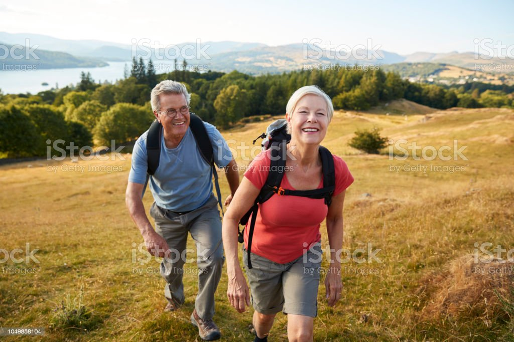 Portrait Of Senior Couple Climbing Hill On Hike Through Countryside In Lake District UK Together royalty-free stock photo